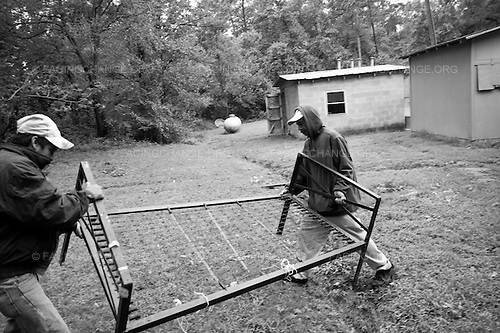 Clinton, North Carolina<br /> September 2011<br /> <br /> After working a 12 hour shift workers in the fields.  Francisco left and his friend take out a spring bed from the room to fix it.