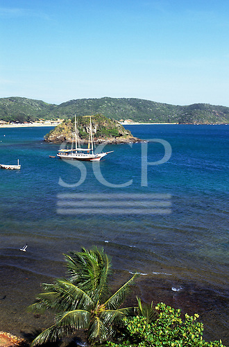 Buzios, Rio de Janeiro State, Brazil. Yacht at anchor next to the Morro Humaita with a palm tree in the foreground.