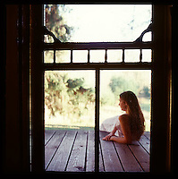 Looking through screen door at woman sitting on porch<br />