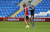 CARDIFF, WALES - SEPTEMBER 05: A member of coaching staff sees to the shirt of Gareth Bale (L) during the Wales training session, ahead of the UEFA Euro 2016 qualifier against Israel, at the Cardiff City Stadium on September 5, 2015 in Cardiff, Wales.
