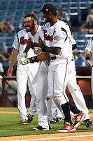 Nashville Sounds second baseman Eugenio Velez (4) celebrates with catcher Matt Pagnozzi (10) after hitting a walk off home run during the first game of a double header against the Omaha Storm Chasers on May 21, 2014 at Herschel Greer Stadium in Nashville, Tennessee.  Nashville defeated Omaha 5-4.  (Mike Janes/Four Seam Images)
