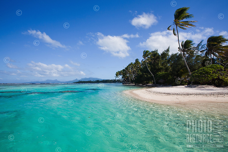 Palm lined islet with white sand beach as seen from lagoon