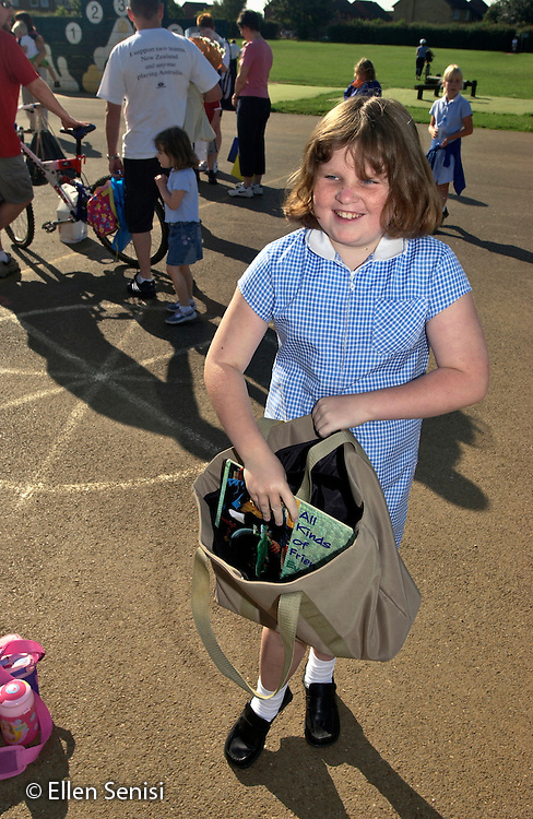 MR / Abingdon, Oxfordshire, England.Thomas Reade Primary School.Girl (9, with special educational needs - S.E.N.) smiles and takes book out of the bag in schoolyard. Encouraging reading at home helps children of varying abilities to do better in school..MR: Web2.©Ellen B. Senisi