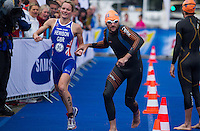 26 AUG 2012 - STOCKHOLM, SWE - Tim Don (GBR) of Great Britain (right) runs to the swim after being tagged by team mate Katie Hewison (GBR) during the 2012 ITU Mixed Relay Triathlon World Championships in Gamla Stan, Stockholm, Sweden .(PHOTO (C) 2012 NIGEL FARROW)