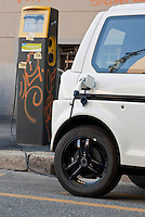 Milano, un veicolo elettrico in carica presso una colonnina --- Milan, an electric vehicle charging battery at an electrical pedestal