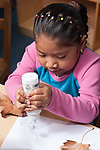 Education preschool 3-4 year olds art activity girl squeezing glue onto paper gluing fall leaves