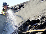 East Hartford firefighter Lackman,  works through a hole in the roof directing water on a hot spot. Thursday, April 16, 2009, during a two-alarm fire at a multi family home at 1437 Main Street in East Hartford. The fire left 11 people homeless and injured one firefighter. (Jim Michaud/Journal Inquirer)