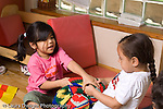 Preschool 4-5 year olds Two girls struggling over possession of blanket in pretend play area horizontal