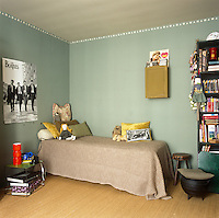A young girl's bedroom with green painted walls and natural flooring. The room is furnished with a single bed with a blanket cover and a free standing shelving unit.