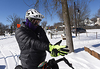 """BUNDLED UP TO BIKE<br />Andrew Herbert of Bentonville pulls on gloves Tuesday Feb. 16 2021 and wears ski goggles for a mountain bike ride in the snow. Herbert started his ride near Compton Gardens in downtown Bentonville. Herbert's advice for off-road biking in the snow? """"Slow down on the turns."""" Go to nwaonline.com/210217Daily to see more photos.<br />(NWA Democrat-Gazette/Flip Putthoff)"""