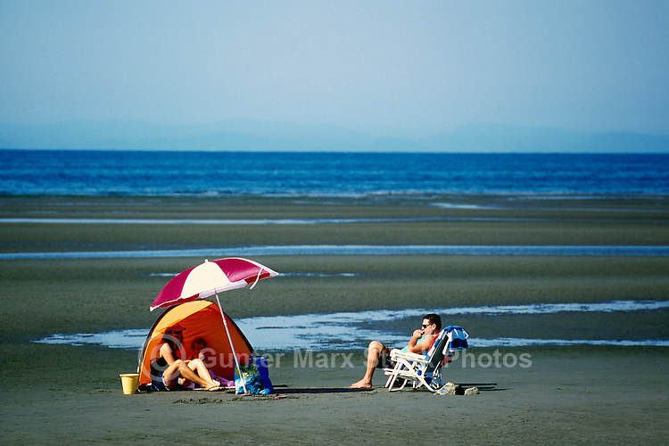 Summer Recreational Activities at White Rock, BC, British Columbia, Canada - Family sunbathing on Sandy Beach along Semiahmoo Bay