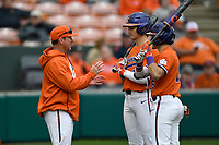 Head coach Monte Lee (18) of the Clemson Tigers talks with Bryce Teodosio, center, and Bo Majkowski during a pitching change in a game against the South Alabama Jaguars on Opening Day, Friday, February 15, 2019, at Doug Kingsmore Stadium in Clemson, South Carolina. Clemson won, 6-2. (Tom Priddy/Four Seam Images)