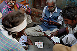 Old artisans playing game of card at Katputly colony in New Delhi, India. 14.11.2009. Kathputly colony is a slum area in West Delhi. This slum seems like any other slum areas of modern India with dysfunctional electricity, non existing sanitation and poverty. As a part of Delhi, this is also ailed with water crisis. Large families live their lives crammed together in a single room with all the odds which complement poverty. One thing which differentiates this slum with any other is the people living in the colony. Nearly everybody in this slum is a traditional performing artist; and they have been migrating to this area for last 50 years from different parts of the country for a better livelihood. They are magicians, acrobats, jugglers, puppeteers, dancers and musicians. These artistes perform in star rated hotels, marriage ceremonies of the richer section, functions, and festivities all around the country and the world. Most of the artisans I met here, have performed in Europe and America but such opportunities are rare to come by. They struggle to keep their art form alive. They say that they don't get any help or support from the government for their basic needs and for the well being of the Kathputly colony -  though they have uphold the prestige of the country internationally. Polluted air, dirty alleys smelling of urine, colourful dress and sound of music characterise Kathputly colony, which is the one of its kind in India. Arindam Mukherjee