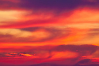 A segment of sky, painted by the setting sun, provides an abstract image of orange and red.