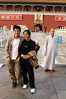 CHINA. Beijing.  Two tourists and a monk in front of the famous Mao Zedong portrait that hangs on the 'Gate of Heavenly Peace' which leads into the Forbidden City and is opposite Tiananmen Square. Mao is still revered in China even 30 years after his death and 40 years since the end of the 'Cultural Revolution' and the 'Great Leap Forward' where it is alleged he was responsible for the death of some 20 million Chinese people. Nevertheless, every day thousands of Chinese people make the pilgrimage to stand and have their photo taken in front of his most famous portrait. 2005.