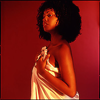 African American woman holding up pink satin sheet<br />