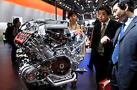 Chinese visitors look carefully at an Audi engine at the 9th Beijing International Automotive Exhibition in Beijing, China.