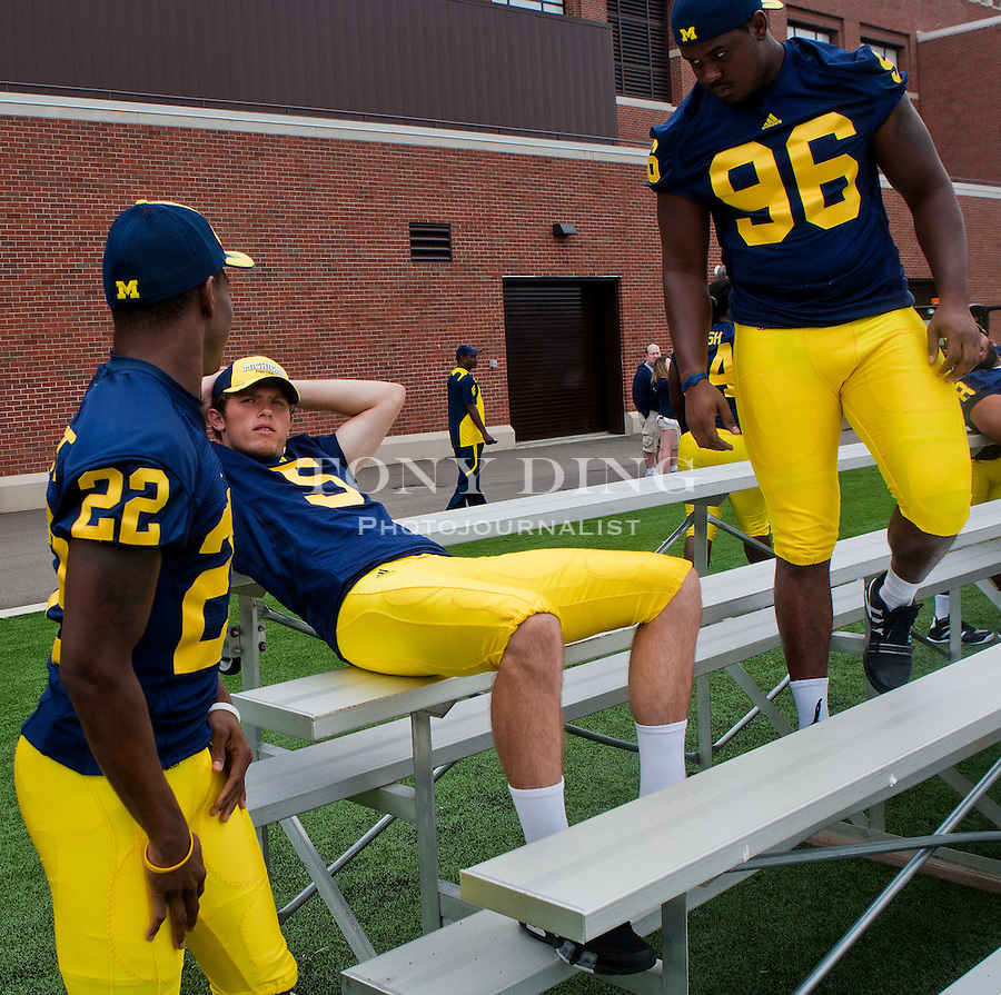 Michigan wide receiver Darryl Stonum (22) talks to quarterback Tate Forcier (5), relaxing between photo sessions, with defensive tackle Terry Talbott (96) listening in, at the annual NCAA college football media day, Sunday, Aug. 22, 2010, in Ann Arbor, Mich. (AP Photo/Tony Ding)
