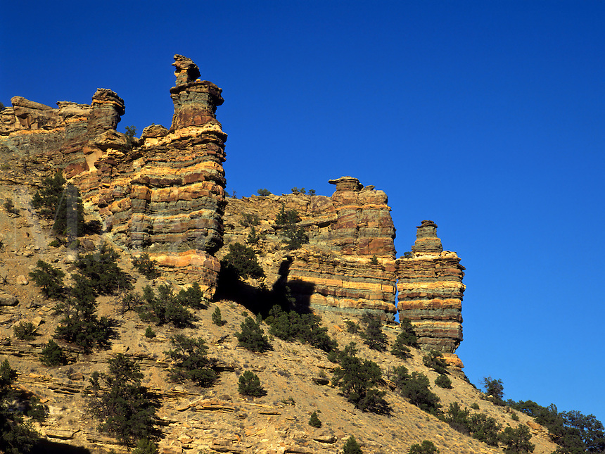 Art in Nature 9409-0176 - Rock Hoodoos in Nine Mile Canyon; earth tones of formations in contrast to deep blue sky. Rocky Mountains, Utah.