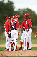 GCL Nationals pitching coach Michael Tejera (left) talks with relief pitcher Diomedes Eusebio (right) as catcher Joey Harris (4), shortstop Carter Kieboom (back left) and third baseman Anderson Franco (back right) listen in during a game against the GCL Astros on August 14, 2016 at the Carl Barger Baseball Complex in Viera, Florida.  GCL Nationals defeated GCL Astros 8-6.  (Mike Janes/Four Seam Images)