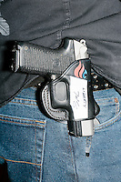 """A pistol in a holster with Ted Cruz's campaign logo and his autograph hangs on the belt of Marc McInnis, of Salem, New Hamsphire, as Texas senator and Republican presidential candidate Ted Cruz speaks at a Second Amendment Rally outside Granite State Indoor Range in Hudson, New Hampshire. Above the autograph, Cruz also wrote """"liberty."""""""