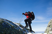 Hiker wearing crampons along the Appalachian Trail (Franconia Ridge Trail), on Franconia Ridge, <br /> in the White Mountains of New Hampshire during the winter months.