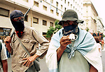 """Economic Turmoil in Argentina<br /> Pickets block the main roads in Buenos Aires to demonstrate against the disastrous economic conditions. Both are masked and one carries a mental pole, while the other  is wrapped in an Argentine flag, masked and drinking Mate through a """"straw"""". Mate is a traditional drink of Argentina. 2000s 2002"""