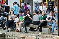 Suzhou, Jiangsu, China.  Chinese Tourists Resting alongside a Canal in Tongli Ancient Town near Suzhou.