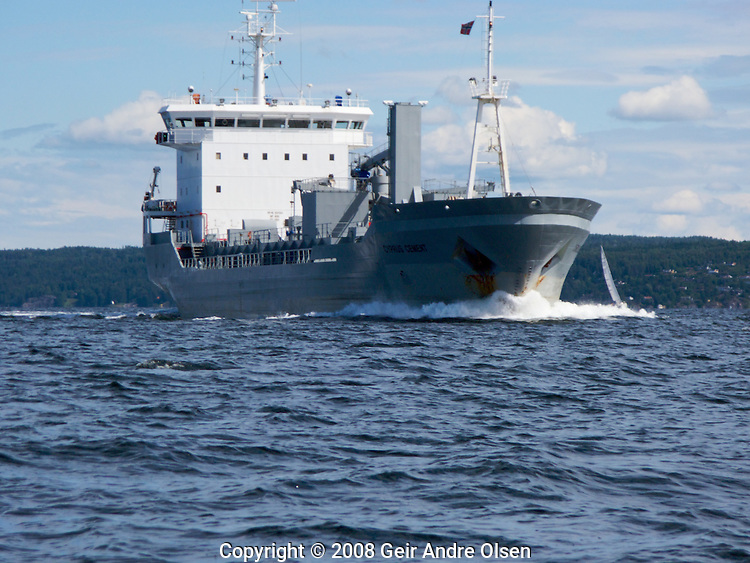 A cargo-ship passes close to a sailboat in the ocean outside the Hurum peninsula in Oslofjord, Norway