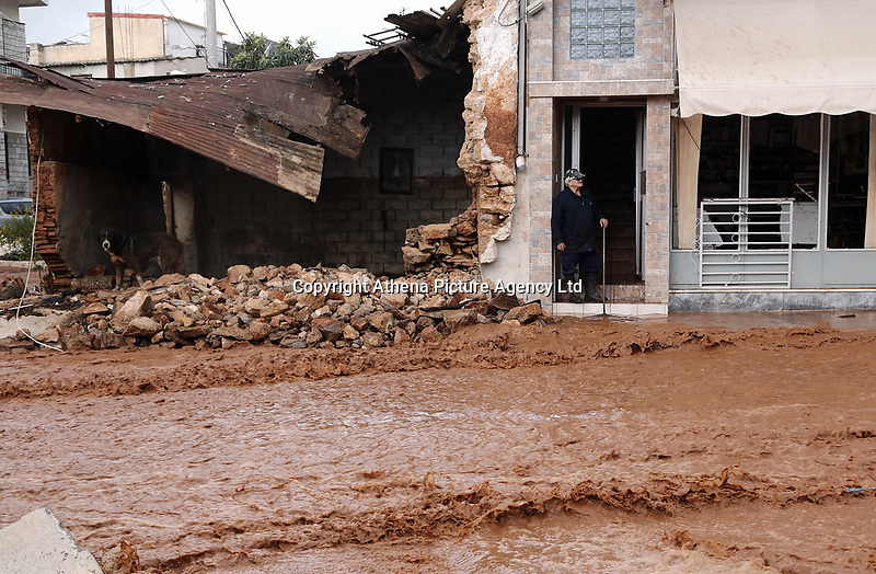 Pictured: A man stands in the doorway of his house watching on the flooded road.<br /> Re: Five people have reportedly died and severe damage caused by heavy rain and flash flooding in the area of Mandra, near Athens, Greece. Wednesday 15 November 2017