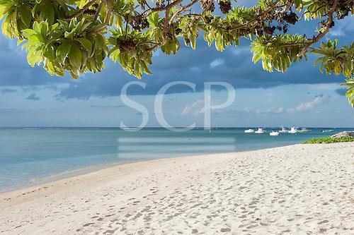 Flic en Flac, Mauritius. La Pirogue tourist resort green tree,  blue sea and white boats and white sand.
