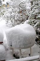 Winter snow piled high on a garden table.