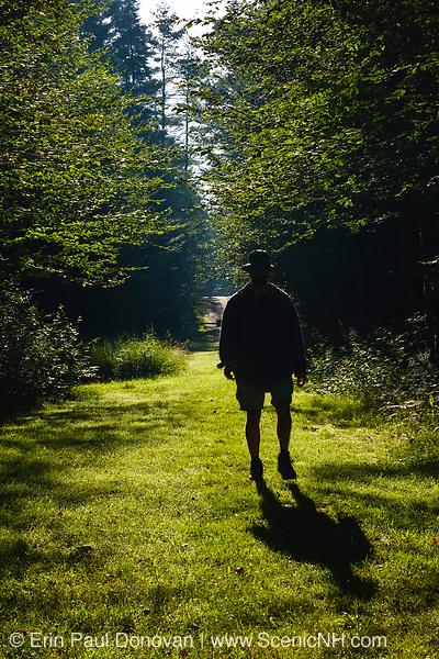 Silhouette of a man walking down path at Bretzfelder Memorial Park in Bethlehem, New Hampshire.
