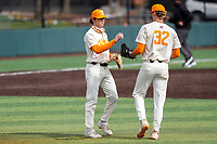 Tennessee Volunteers third baseman Jake Rucker (7) hands the baseball to relief pitcher Sean Hunley (32) during the game against the LSU Tigers on Robert M. Lindsay Field at Lindsey Nelson Stadium on March 28, 2021, in Knoxville, Tennessee. (Danny Parker/Four Seam Images)