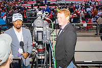 Mike Nificent (left) and Alex Caldwell, commentators on the rightwing Right Side Broadcasting Network, prepare to broadcast from the press riser before the arrival of US President Donald Trump at a Make America Great Again Victory Rally in the final week before the Nov. 3 election at Pro Star Aviation in Londonderry, New Hampshire, on Sun., Oct. 25, 2020. Right Side Broadcasting Network is an online network devoted to showing full-length Trump campaign rallies.