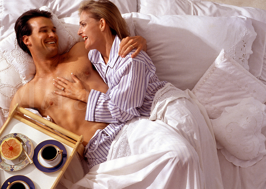 A smiling young couple with breakfast in bed.