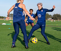 ORLANDO, FL - JANUARY 21: Julie Ertz #8 nutmegs Megan Rapinoe #15 of the USWNT during a training session at the practice fields on January 21, 2021 in Orlando, Florida.