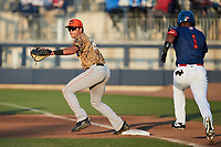 Down East Wood Ducks first baseman Dustin Harris (20) waits for a throw as Johnabiell Laureano (1) of the Kannapolis Cannon Ballers hustles down the line at Atrium Health Ballpark on May 8, 2021 in Kannapolis, North Carolina. (Brian Westerholt/Four Seam Images)
