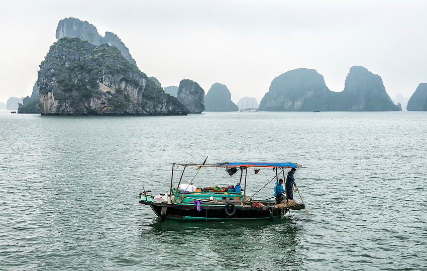 """A fisherman plies his trade from a boat in Ha Long Bay. Ha Long Bay, located on the east coast of Vietnam near Haiphong, contains over 1,900 limestone """"karst"""" islands projecting from the sea, frequently shrouded in fog, mist and rain."""