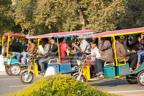 Delhi, India. Three crowded motorized auto rickshaws.