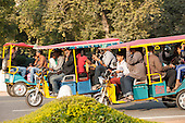 Delhi, India. Three crowded motorized auto rickshaws.