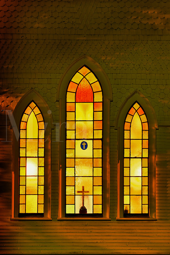 Illuminated church windows at night.