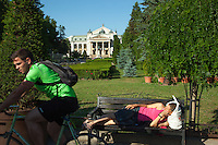 """Romania. Iași County. Iasi. A woman lies on a bench while a man rides his bicycle. In the background, the """"Vasile Alecsandri"""" National Theatre and the National Theatre park. The """"Vasile Alecsandri"""" National Theatre, opened in 1840, is the first National Theatre in Romania. The building, designed according to the plans of the Viennese architects Hermann Helmer and Ferdinand Fellner, was raised between 1894 and 1896. Iași (also referred to as Iasi, Jassy or Iassy) is the largest city in eastern Romania and the seat of Iași County. Located in the Moldavia region, Iași has traditionally been one of the leading centres of Romanian social life. The city was the capital of the Principality of Moldavia from 1564 to 1859, then of the United Principalities from 1859 to 1862, and the capital of Romania from 1916 to 1918. 5.06.15 © 2015 Didier Ruef"""