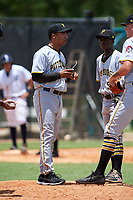 GCL Pirates manager Elvin Nina (27) talks with pitcher Austin Shields (right) and second baseman Victor Ngoepe (5) during a game against the GCL Tigers West on July 17, 2017 at TigerTown in Lakeland, Florida.  GCL Tigers West defeated the GCL Pirates 7-4.  (Mike Janes/Four Seam Images)
