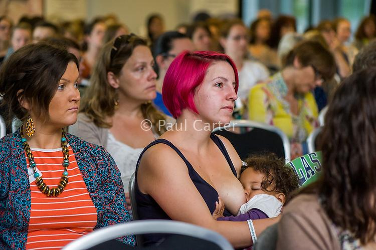 A mother  listening to a speaker while breastfeeding her toddler in the auditorium at a conference.<br /> <br /> 13/06/2015
