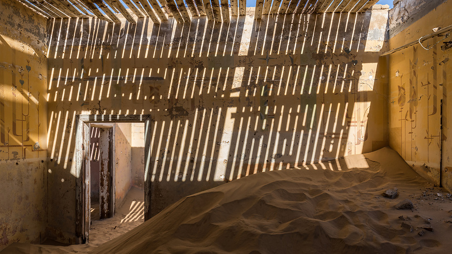 The Sun Shines Through The Remaining Roof Slats In A Building In The Deserted Mining Town Of Kolmanskop.