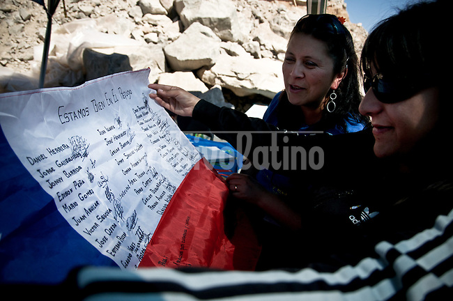 Cristy Coronado (40) wife of Juan Carlos Aguilar (49). Her husband is one of the 33 miners trapped inside the mine since 5 of agoust and Carola Lobos, doughter of Franky Lobos are holding a flag sent from inside the mine. Relatives of miners trapped 700 meters under the ground since August 5th reacts emotionally to the news that miners could soon be rescued.