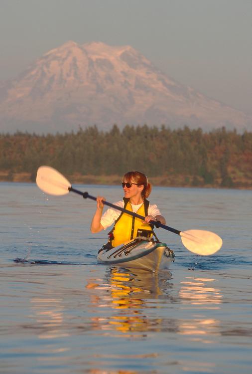 Woman sea kayaker, Puget Sound, Mount Rainier, Nisqually Reach; Washington State; Pacific Northwest; USA; Cascadia Marine Trail;.