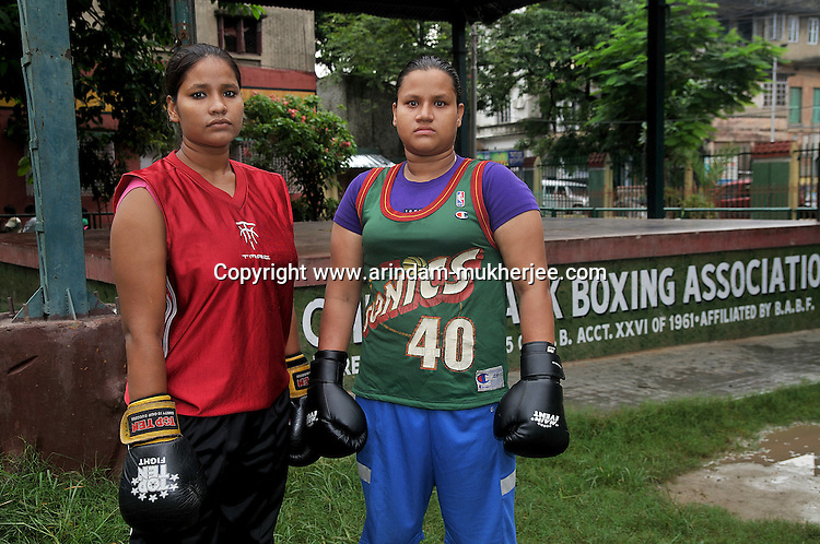 INDIA (West Bengal - Calcutta), August 2010,Shakila Babe(right) and Sanno Babe (left) standing in front of their boxing association. Shakila and Shanno are twins from a poor muslim family of Iqbalpur, Kolkata. . Inspite of their late father's unwillingness to send his daughters to take up  boxing her mother Banno Begum inspired them to take up boxing at the age of 3. Their father was more concerned about the social stigma they have in their community regarding women coming into sports or doing anything which may show disrespect to the religious emotions of his community. Shakila now has been recognised as one of the best young woman boxers of the country after she won the  international championship at Turkey in the junior category. Shanno is also been called for the National camp this year. Presently Shakila and shanno has become the role model in the Iqbalpur area  and parents from muslim community of Iqbalpur have started showing interst in boxing. Iqbalpur is a poor muslim dominated area mostly covered with shanty town with all odds which comes along with poverty and lack of education. - Arindam Mukherjee
