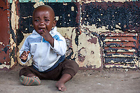 A baby cries outside one of Durban Deep Goldmine's hostels on the outskirts of Johannesburg, South Africa.